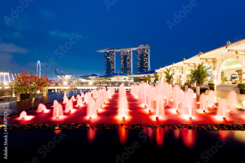 Poster Marina Bay Sands and a colorful fountain at night in Singapore.