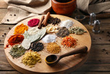 Board with different aromatic spices on wooden table