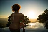 junge Frau schaut im Swimmingpool den Sonnenuntergang an