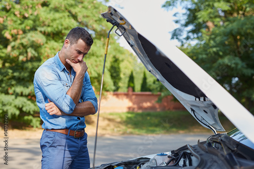 Stressed man standing by a broken car on the road