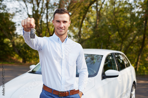 Handsome man with the key standing in front of car