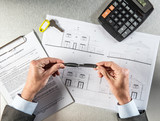 builder hands with key and housing draft thinking about negotiation - 141738931