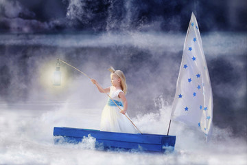 Fairytale photography. A girl sailing on a boat in the fog. Keeps the light in the hands.