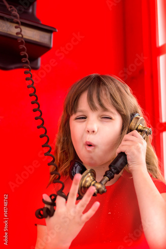 Young girl speaking on the telephone in red cabin Poster