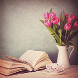 Open book, a cup of tea and pink tulips in a vase - 141751597