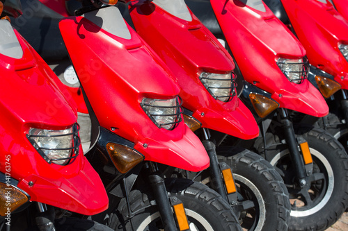 Foto op Canvas Scooter red scooters or motorcycles for sale or hire in row