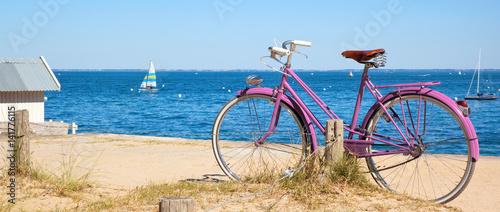 Vélo rose devant la plage