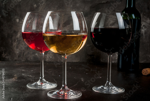 Selection of three kinds (Varieties) of wine - red, white and pink. In glasses, with an open bottle. On a dark concrete background. Copy space © ricka_kinamoto