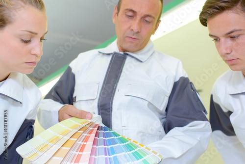 Decorators looking at color charts