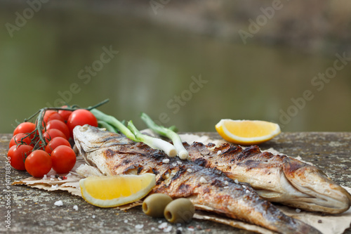 Grilled fish served on a paper with tomato,m onion and olives and decorated with rosemary and lemon