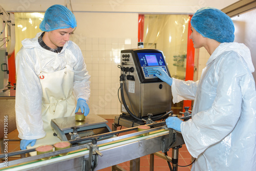 Factory workers setting up production line Poster