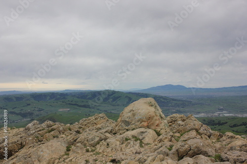 Rocky outcropping overlooking green valley Poster