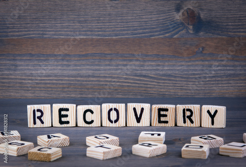 Recovery word written on wood block. Dark wood background with texture. Photo by tumsasedgars