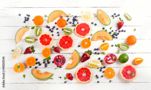 Fresh mixed fruits on white wooden background. Healthy food concept.