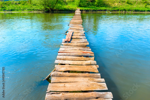 Fototapeta Old wooden bridge through the river