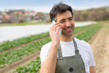 Portrait of an attractive middle aged farmer using smartphone on a field - Nature concept