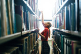 Young librarian searching books and taking one book from library bookshelf