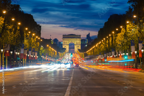 Wall mural Night view of Paris traffic in Champs-Elysees street and the Arc de Triomphe in Paris, France.