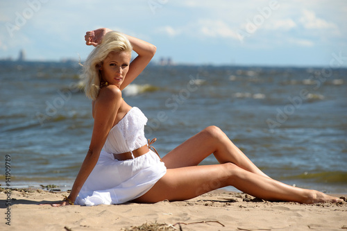 Beautiful sexy blonde in white dress sitting on the seashore