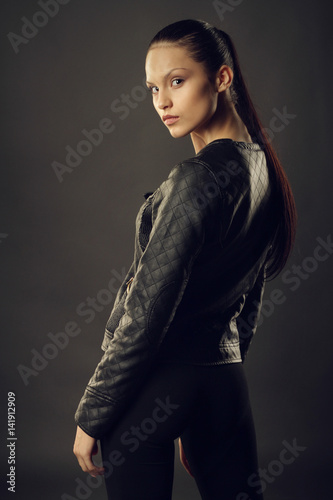 Poster Beautiful girl in black leather jacket and black leggings posing on a gray background