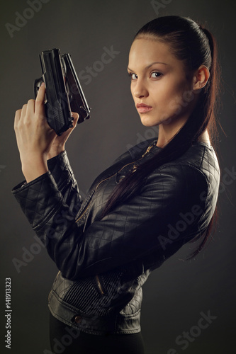 Poster Beautiful girl in black leather jacket posing with two pistols in their hands