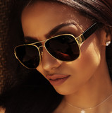 Beautiful woman with golden sun tan wearing shades sunglasses
