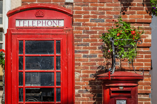 Traditional red post box and the phone booth near a brick wall in Sidmouth, Engl Poster