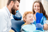 Young boy looking at the mirror with toothy smile sitting on the chair with dentist and assistant at the dental office - 141940713
