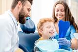 Młody chłopak patrząc w lustro z toothy uśmiech siedzi na krześle z dentystą i asystentem w gabinecie stomatologicznym