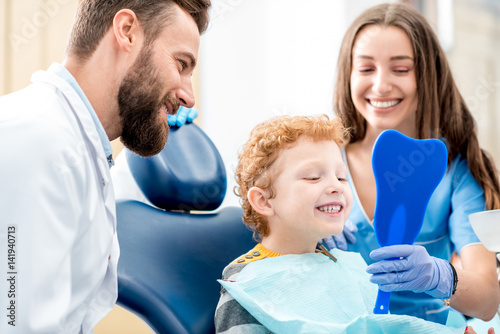 obraz lub plakat Young boy looking at the mirror with toothy smile sitting on the chair with dentist and assistant at the dental office