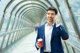 Attractive middle aged business man having a call on the way to office - Business concept