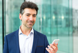 Attractive middle aged business man checking email on his smartphone on the way to office