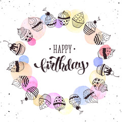 Happy birthday greeting card with watercolor spots on white background.  Hand drawn calligraphy with circle frame from cupcakes. Birthday vector illustration in romantic style.