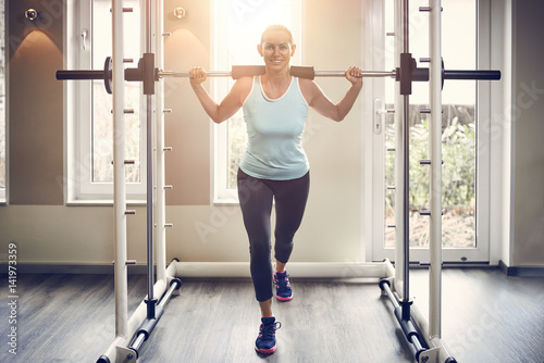 Attraktive blonde Frau trainiert mit Gewichten Poster