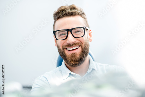 Plakát Handsome businessman with great smile sitting on the dental chair