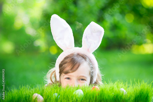 Fotografiet Easter bunny and eggs on green grass