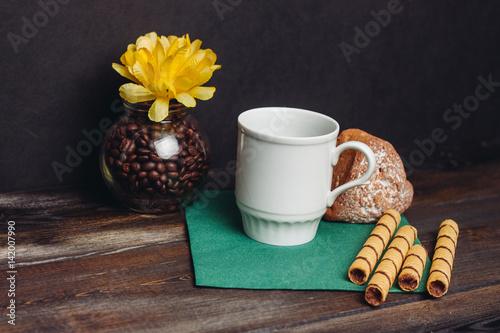 white mug on a green napkin, cupcake, sweet straw and a flower © ageevphoto