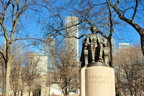 The Head of State bronze stature, also called Seated Lincoln, is located in Chicago's Grant Park. The piece was created by Augustus Saint-Gaudens. In the background is part of the city skyline.