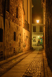 Narrow street in Old Town of Torun at night. Poland. Europe.