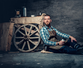 A man sits on a floor and drinks coffee.