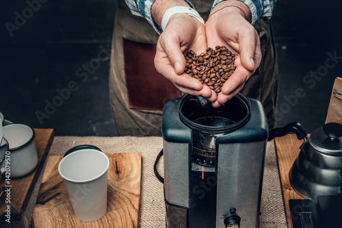 Close up image of a man putting coffee beans into a coffee machine.