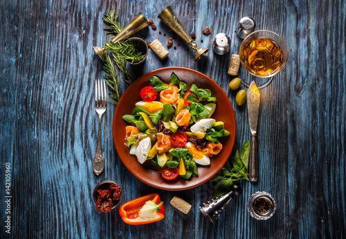 Delicious fresh salad with seafood on the old wooden background