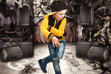 Fototapety The little boy in the style of Hip-Hop . Children's fashion.Cap and jacket. The Young Rapper.Graffiti on the walls.Cool rap dj.