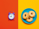 photo of alarm clock and cookies on the wonderful colorful background in pop art style