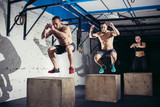 Fototapety Group of athletic people jumpin over some boxes in a cross-training gym