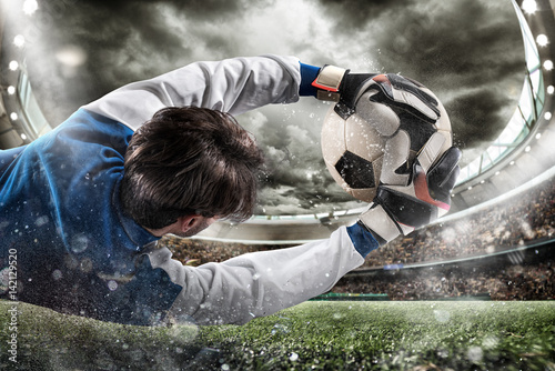 Fototapeta Goalkeeper catches the ball in the stadium