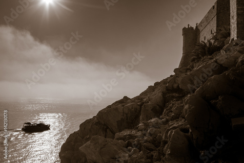 Silhouetted tourist boat by the old town walls in Dubrovnik Poster