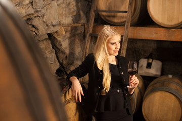 Beautiful young blond woman drinks wine in wine cellar