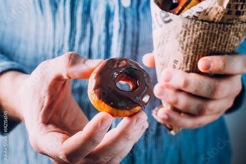 Poster Man holding Fresh homemade donuts glazed chocolate