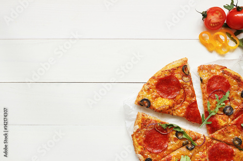 Canvas Pizzeria Fresh delisious sliced pizza on the wooden table with copy space, top view